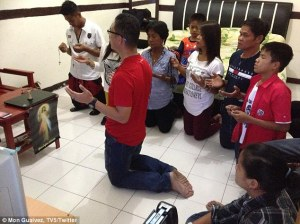The Veloso family in prayer. Photo by dailymail.co.uk